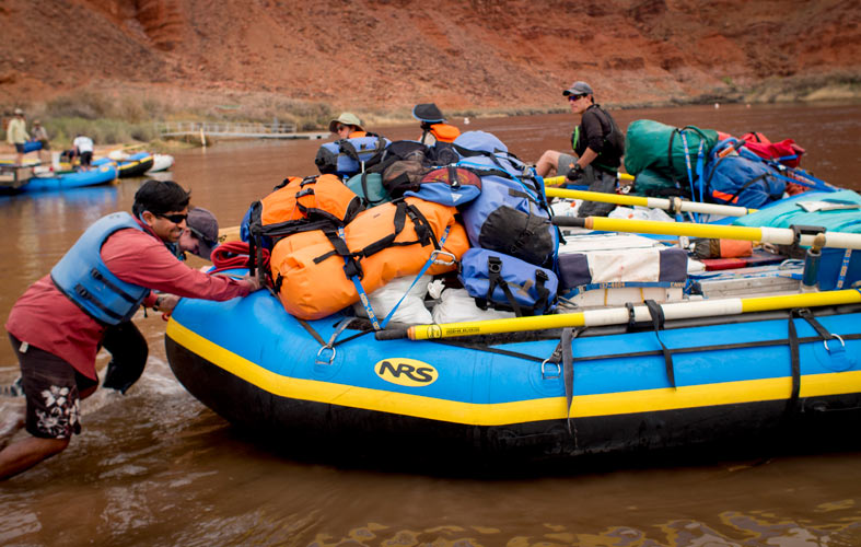 A group of team members launches a gear-filled raft onto the Colorado River