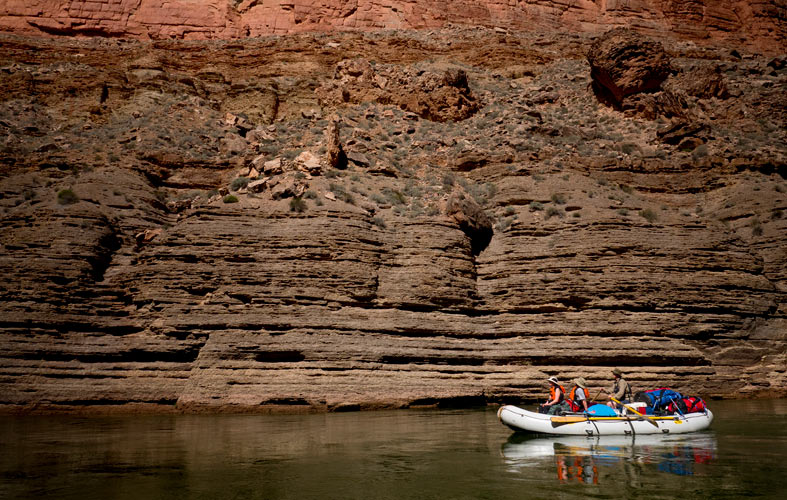 A raft floats down the river in front of a wall containing millions of years of sedimentary rock
