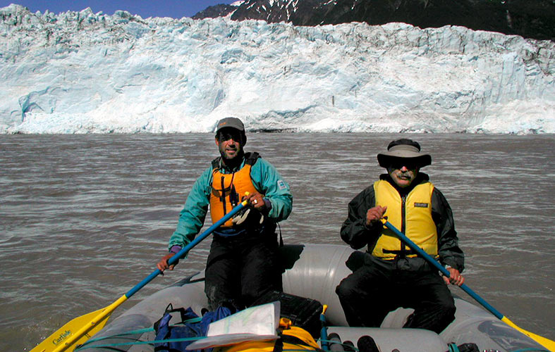 two men paddle a boat with a glacier visible in the background